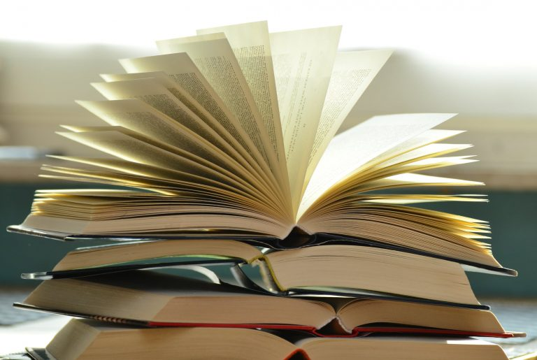 Stock image of several open books piled on each other.